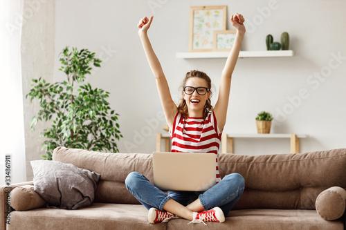 Obraz na plátně Glad woman celebrating good news while working on laptop at home.
