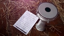 Music Sheet And Drum Doumbek On Wooden Floor With Straw