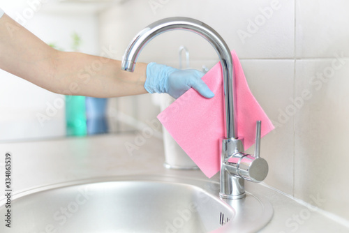 Obraz Woman in gloves cleaning kitchen. - fototapety do salonu