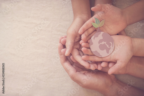 Hands holding growing tree on earth, save planet, earth day, ecology environment, climate emergency action, csr social responsibility, sustainable living, world environment day concept