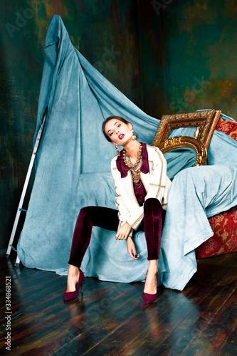 beauty rich brunette woman in luxury interior near empty golden frames, lifestyl Canvas Print