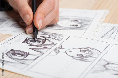 Artist drawing an anime comic book in a studio. - 334871515