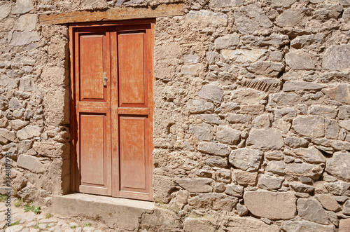Wooden door at the entrance of a traditional clay house at a sunny day on a stre Canvas Print