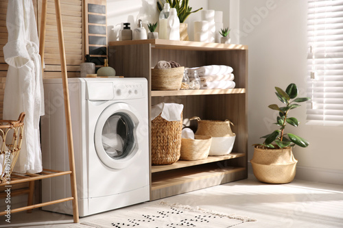 Modern washing machine and shelving unit in laundry room interior фототапет
