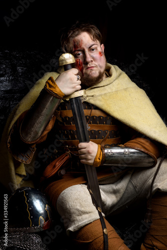 A Scandinavian warrior viking wounded in leather and metal armor with a fighting sword and helmet on a dark background Fototapeta