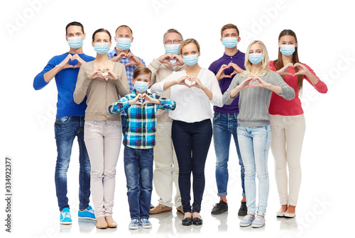 Obraz health, quarantine and pandemic concept - group of people wearing protective medical masks for protection from virus showing hand heart gesture - fototapety do salonu