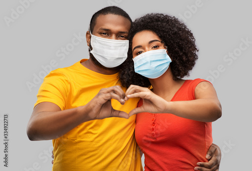 Obraz health, quarantine and pandemic concept - happy african american couple wearing protective medical masks for protection from virus making hand heart gesture over grey background - fototapety do salonu