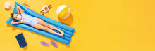 Top View On A Little Girl In A Swimsuit And A Protective Mask Resting On An Inflatable Blue Mattress On A Yellow Background, Concept Of Summer Vacation. Banner Copy Space