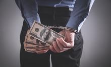 Businessman In Handcuffs Holdi...