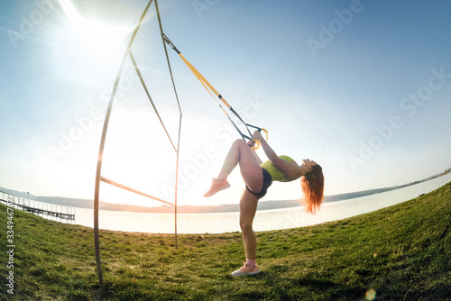 Cuadros en Lienzo beautiful woman exercising with suspension straps TRX   outdoors near the lake at daytime