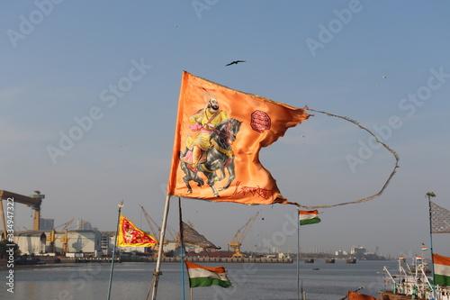 Mumbai, Maharastra/India- March 31 2020: Waving saffron flag of the Maratha Warrior in clear sky Wallpaper Mural