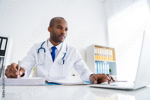 Photo of family doc dark skin successful professional guy write prescriptions patients base journal use online statistics notebook wear white lab coat sit chair modern office clinic indoors