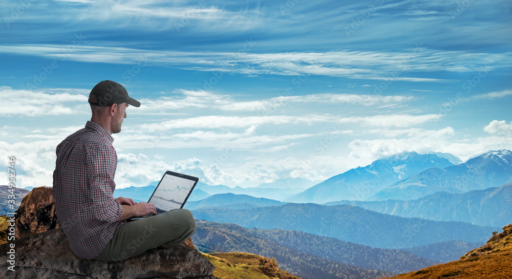 Fototapeta man working remotely outdoors with laptop