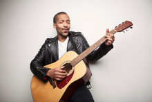 African Bearded Man Playing Guitar Wearing Leather Black Jacket Isolated On White Background.