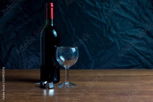Botella de vino tinto junto a copa de cristal  y tapón de metal en mesa de madera y sobre fondo oscuro Canvas Print