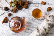 Chaga Mushrooms Infusion In Glass Teapot On White Board. View From Above. Useful Coffee Alternative To Boost Immunity During The Virus.
