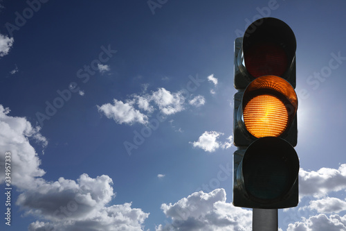 Photo Semaforo con luce gialla accesa, sfondo del cielo, vista verticale