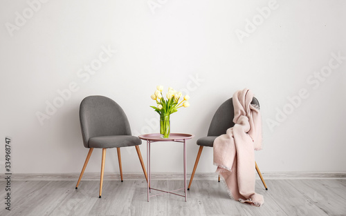 Papel de parede Vase with beautiful flowers on table and comfortable chairs in room
