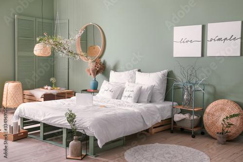 Obraz Interior of beautiful modern bedroom with spring flowers - fototapety do salonu