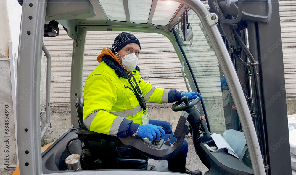 Fototapeta coronavirus : man with protective mask and gloves drives the forklift