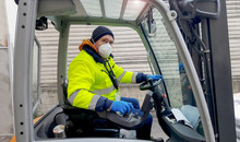 Coronavirus : Man With Protective Mask And Gloves Drives The Forklift