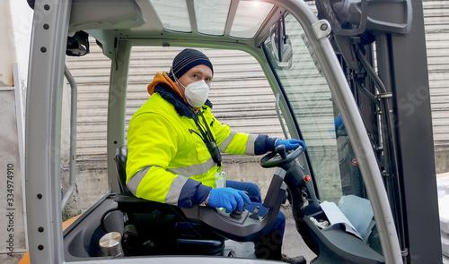 Fototapeta coronavirus : man with protective mask and gloves drives the forklift obraz