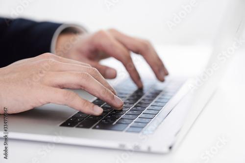 Fototapeta ノートパソコンでタイピングする日本人男性ビジネスマン obraz