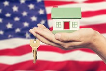 Hand Holding A Model Of House And Key On The USA Flag Background