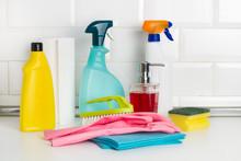 Productos De Limpieza: Botellas, Aerosoles, Pulverizador, Paño, Esponja, Guantes De Látex, Cepillo Sobre Una Mesa De La Cocina Encimera Y Fondo Blanco De Azulejos Cuadrados Metro. Vista De Frente