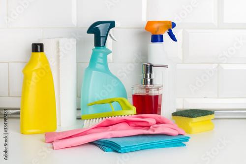 Fotografia Productos de limpieza: botellas, aerosoles, pulverizador, paño, esponja, guantes de látex, cepillo sobre una mesa de la cocina encimera y fondo blanco de azulejos cuadrados metro