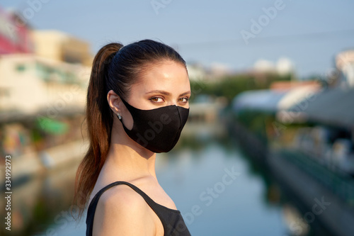 Fotografija Dark-haired woman with a braid wearing a mask to protect herself from the covid-19 coronavirus in Bangkok, Thailand