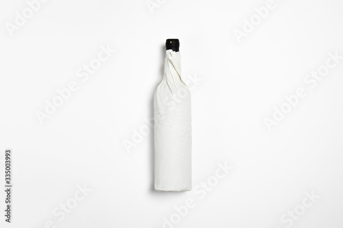 Cuadros en Lienzo Bottle of Red Wine Mock-up wrapped in craft paper on white background