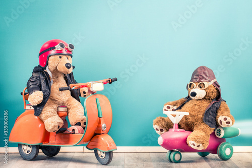 Photographie Retro Teddy Bear toy in helmet with goggles on old children's pedal  scooter from 60s and Teddy Bear in leather aviator hat front mint blue background