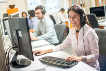 Friendly Female Operator Consulting Client On Hotline In Call Center