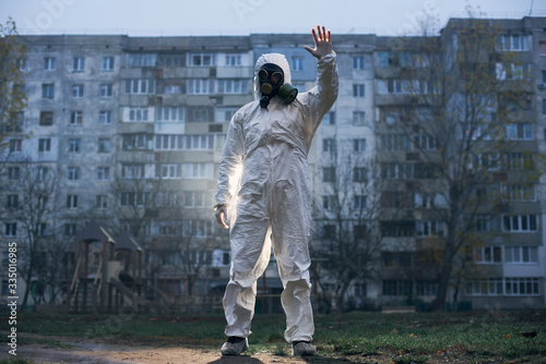 Male ecologist standing in front of high block of flats, showing stop sign, low angle view, concept of environment pollution Fototapet