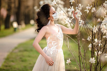 Portrait Of A Beautiful Young Bride In A Wedding Dress And A White Medical Mask On Her Face Near A Blooming Magnolia. Crown Virus. Covid 19 Protection Against The Virus