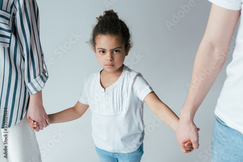 adopted african american child holding hands with divorced parents isolated on grey