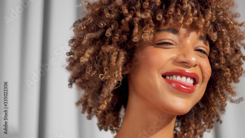 Adult mixed race black woman with curly hair on grey curtains background Smiling wide wear daily natural makeup