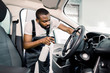 Young African male worker in uniform cleaning car interior and steering wheel with special cleaning chemical spray. Chemical and wet cleaning, car detailing concept