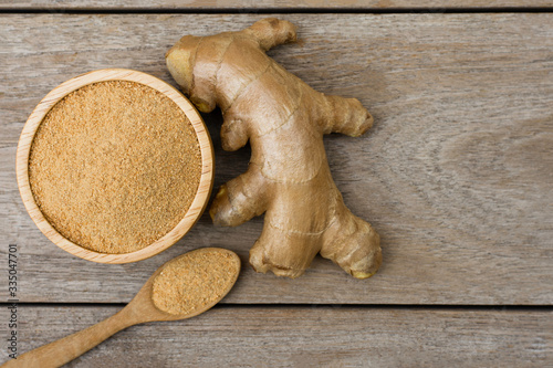 Obraz na plátne Fresh ginger powder in wooden bowl and spoon with ginger root isolated on wooden table background