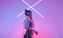 Beautiful Asian Woman In A Raincoat Listens Music In Headphones Around Colourful Neon