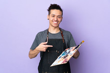 Young Artist Man Holding A Palette Over Isolated Purple Background And Pointing It