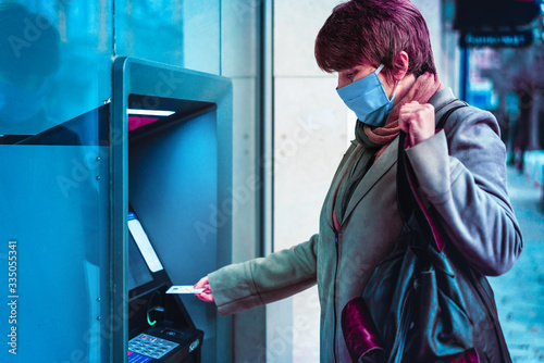 Photo Woman with protective mask standing on city street and using ATM machine