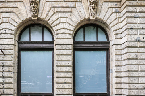 Fotografia, Obraz A sculpture of Medusa's head with snakes and a sculpture of a mature bearded man's head adorn the keystones above a pair of window arches on an old building in Budapest, Hungary