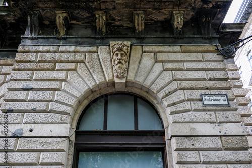 Fototapeta A sculptured bearded man's head adorns a keystone above a window arch