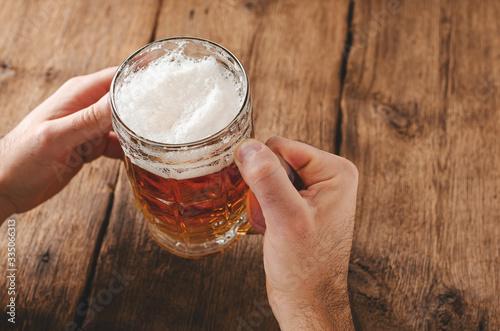 Fototapeta Male hands holding full glass of blonde beer