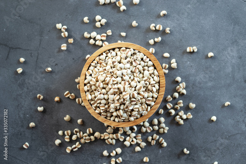 Tablou Canvas white Job's tears ( Adlay millet or pearl millet ) in wooden bowl on dark cement background, top view image