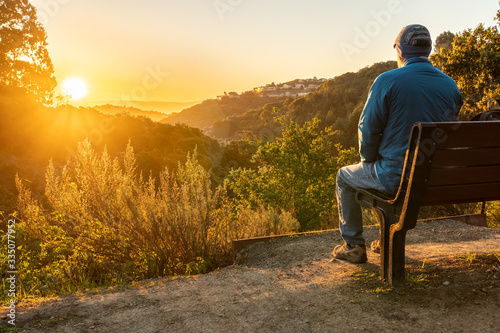 Fototapeta Person, man, sitting on a bench watching the sunrise over hills and valley with trees and shrubs in the middle and houses on a hill in the background obraz
