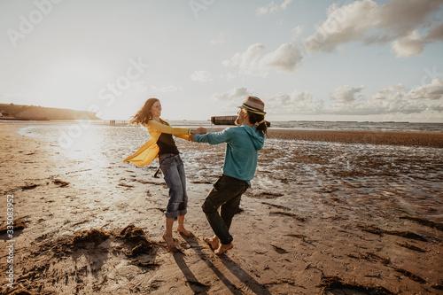 Obraz na plátně Glückliches Paar mit Lebensfreude am Strand