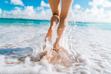 Legs Of A Beautiful Young Girl Who Runs Towards The Ocean On A Sandy Beach. Vacation On The Paradise Beaches Of Asia. Summer And Vacation Holiday Concept. Ocean Foam Wraps Around The Girl's Legs. Phot